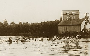 Duck Pond, now known as Swan Lake, was the scene of the freshmen-sophomore Rope Pull until the 1950s. This photo shows the 1915 event. The brick building in the background is Storrs Hall.