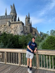 Photo of Austin Callahan smiling in front of a theme park castle